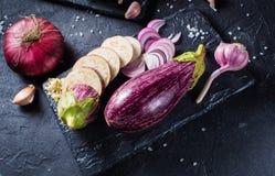 Etwas Auberginen, Knoblauch und rote Zwiebel auf einem schwarzen Brett und einem backgr stockfotografie