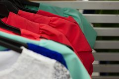 Etwas benutzte Kleidung, die an einem Gestell in einer Flohmarkt hängt Hintergrund des Kleides Selektiver Fokus stockfotografie