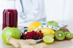 Etwas Früchte wie Äpfel, Kiwis, Zitronen und Beeren auf Ernährungswissenschaftlertabelle lizenzfreie stockbilder