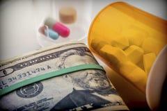 Etwas Medizin nahe bei einem Block von Karten des Dollars, Stockfoto