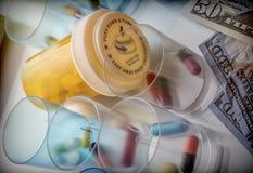 Etwas Medizin nahe bei einem Block von Karten des Dollars Stockbilder