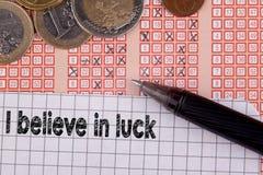 Eu acredito na sorte Pena e bilhete de loteria do loto do bingo com números cruzados Fotografia de Stock Royalty Free