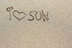 Eu amo as palavras do sol escritas na areia Textura do fundo da areia da praia Fotos de Stock