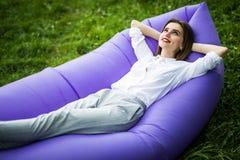 Eu amo holydays Jovem mulher bonita que encontra-se no lamzac inflável do sofá ao descansar na grama no parque no sol fotos de stock royalty free