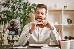 Eu amo o alimento! Retrato do blogger entusiasmado do alimento que come um sanduíche ao em linha fluir em meios sociais imagens de stock