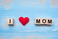 Eu amo o texto da MAMÃ com forma vermelha do coração no fundo de madeira azul Conceitos felizes do dia de mãe e do dia das mulher fotografia de stock