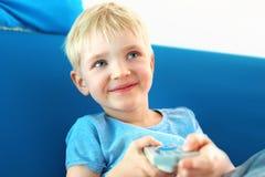 Eu amo a televisão Uma criança com um controlo a distância da tevê Imagem de Stock