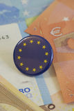 EU badge on Euro notes. European Union badge resting on pile of Euro notes, narrow depth of field Stock Photo