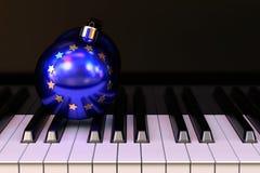 EU Christmas concept. EU Christmas ball on the piano keyboard Stock Photos