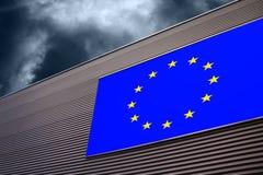 Eu disintegration background. Closeup of European Union flag on the industrial hall facade with dark blue cloudy sky. Conceptual EU disintegration background Royalty Free Stock Photography