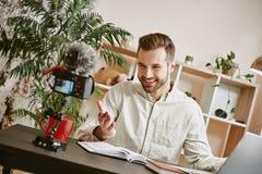 Eu estou tão feliz! Blogger masculino novo alegre que faz um índice novo para seu vlog com a câmara digital montada tripé imagem de stock royalty free