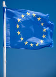 EU flag. In the wind and in the blue sky with its yellow stars Stock Image