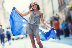EU Flag. Cute happy girl with the flag of the European Union. Young teenage girl waving with the European Union flag in the city Royalty Free Stock Images