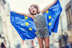 EU Flag. Cute happy girl with the flag of the European Union. Young teenage girl waving with the European Union flag in the city.  royalty free stock images
