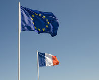 EU flag and the French Flag. EU and French flag flying side by side Royalty Free Stock Photo