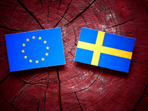 EU flag with Swedish flag on a tree stump stock photography