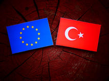 EU flag with Turkish flag on a tree stump royalty free stock images