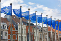 EU Flags Flying in Front of Traditional Houses in Brussels. A line of EU flags flying on metal poles in front of the Berlaymont Building in Brussels with Royalty Free Stock Photography