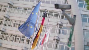 EU flags wave behind a cctv security camera stock video footage