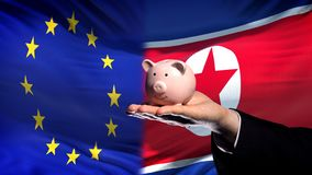 EU investment in North Korea, hand holding piggybank on flag background. Stock photo stock image