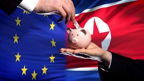 EU investment in North Korea, hand putting money in piggybank on flag background. Stock photo royalty free stock photography