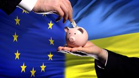 EU investment in Ukraine, hand putting money in piggybank on flag background. Stock photo royalty free stock photos