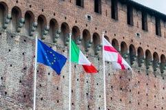 EU-, italienare- och Milan flaggor på Sforza rockerar i Milan, Italien Royaltyfria Bilder