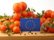 EU kennzeichnen auf einer Holzverkleidung mit den Tomaten, die auf einer Weißrückseite lokalisiert werden Lizenzfreie Stockfotografie