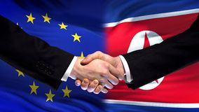 EU and North Korea handshake, international friendship relations flag background. Stock photo stock images