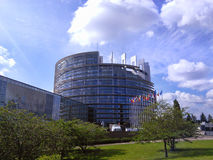 EU parliament entire building with blue sky and clouds above. Wh. Ole building of Europe Union Parliament.Circle modern building with flags before Royalty Free Stock Images