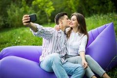 Eu te amo demasiado Assento de beijo dos pares novos no lamzac inflável do sofá e selfie da tomada no telefone ao descansar na gr imagem de stock