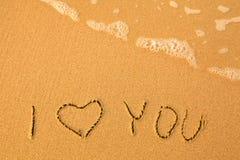 Eu te amo - escrito à mão na areia em uma praia do mar Imagens de Stock Royalty Free