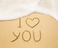 Eu te amo escrito na areia amarela molhada da praia Imagens de Stock