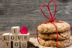 Eu te amo inscrição com coração e a pilha de madeira de cookies caseiros Fotos de Stock