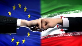 EU vs Iran conflict, international relations crisis, fists on flag background. Stock photo stock images