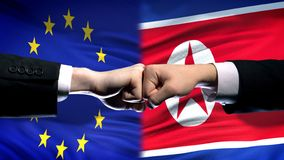 EU vs North Korea conflict, international relations, fists on flag background. Stock photo stock photos