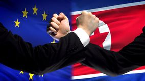 EU vs North Korea confrontation countries disagreement, fists on flag background. Stock photo stock photo