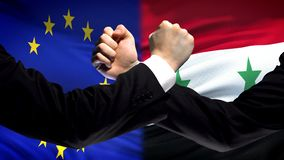 EU vs Syria confrontation, countries disagreement, fists on flag background. Stock photo royalty free stock images