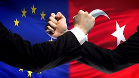 EU vs Turkey confrontation, countries disagreement, fists on flag background. Stock photo stock photography