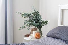 Eucalipto en el interior, café de la mañana en la tabla en el dormitorio por la cama fotos de archivo libres de regalías
