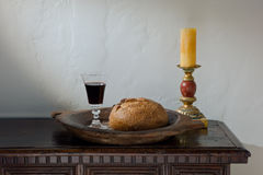 Eucharist. Table with Eucharist symbols of bread, wine, and candle stock photo