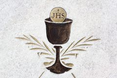 Eucharist - christian sacral ritual with cup, sacramental wine and bread. Icon and pictogram. JHS - Jesus Savior of Mankind stock photos