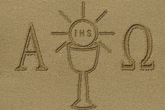 Eucharist symbol. Drawn on a beach sand stock photography