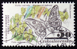 Eudia pavonia and viola sudetica, from the series `Flora and fauna`, circa 1983. MOSCOW, RUSSIA - FEBRUARY 12, 2017: A post stamp printed in CZECHOSLOVAKIA shows Stock Image