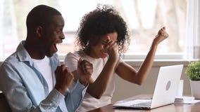 Euforisch Afrikaans paar die die laptop bekijken door online winst wordt opgewekt stock videobeelden