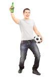 Euforische sportventilator die een bierfles en een voetbal houdt Royalty-vrije Stock Fotografie