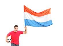 Euforische ventilator die een bal houdt en een vlag golft Royalty-vrije Stock Afbeelding