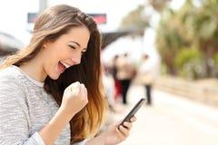 Euforische vrouw die op haar slimme telefoon in een station letten