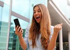 Euforyczna biznesowa kobieta ogląda jej mądrze telefon i pokazuje zwycięzcy gest plenerowego obraz royalty free