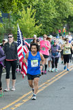 2016 Eugene Marathon. EUGENE, OR - MAY 1, 2016: Runner carrying an American flag to represent the USA and the United States Armed Forces at the 2016 Eugene Royalty Free Stock Photo